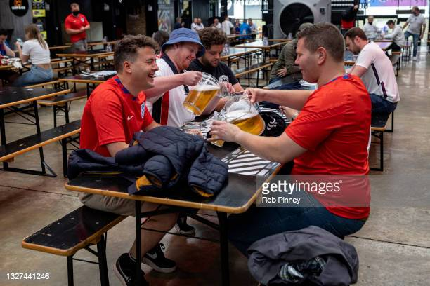 Group of England fans pouring pitchers of beer at Boxpark Wembley on July 07, 2021 in London, England. England has reached the semi-finals of the...