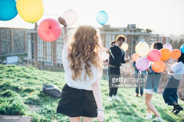 Group of enjoying roof party, holding helium balloons