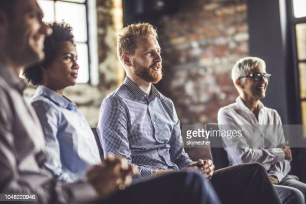 group of entrepreneurs attending a business seminar in a board room. - attending stock pictures, royalty-free photos & images