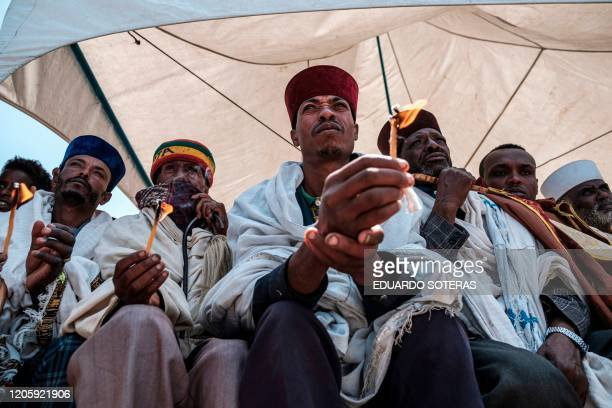 A group of Ethiopian Orthodox priests hold candles during a memorial ceremony at the crash site of the Ethiopian Airlines Flight 302 airplane...