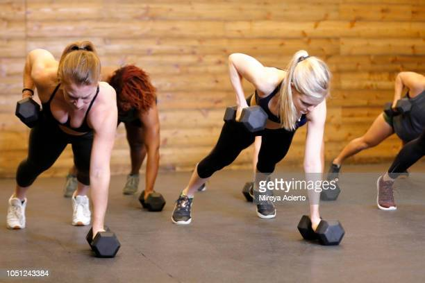 a group of ethnically diverse women working out a the gym with dumbells in a plank position. - blonde forte poitrine photos et images de collection