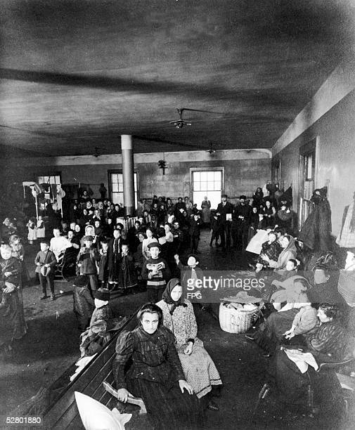 A group of European immigrants including men women and children await the next step on their journey to the United States at the immigration...