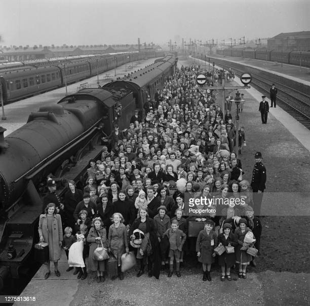 Group of evacuee children and mothers stand together beside their train on a platform at Blackpool Station in Lancashire, England during the Blitz...