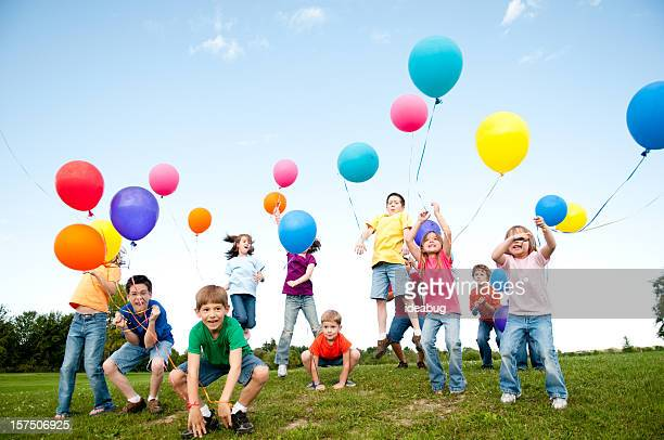 Group of Excited Boys and Girls Celebrating with Balloons