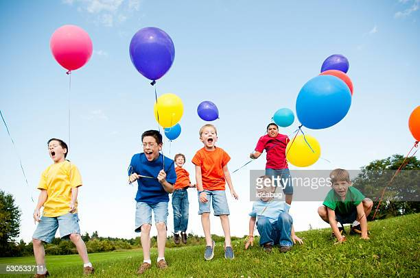 Group of Excited Boys Jumping and Yelling with Balloons Outside