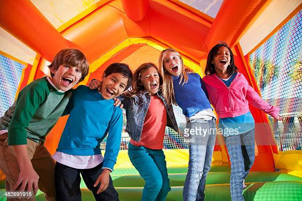 group of excited children in bouncy house - gala stock pictures, royalty-free photos & images