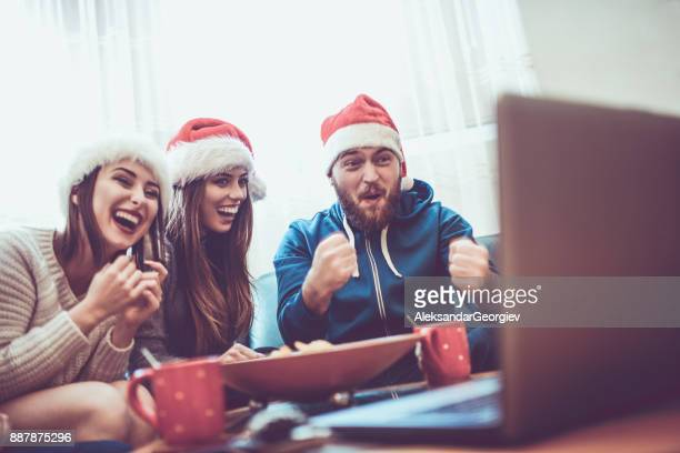 Group of Excited Friend Drink Hot Drink and Watch Funny Movie for The Holidays