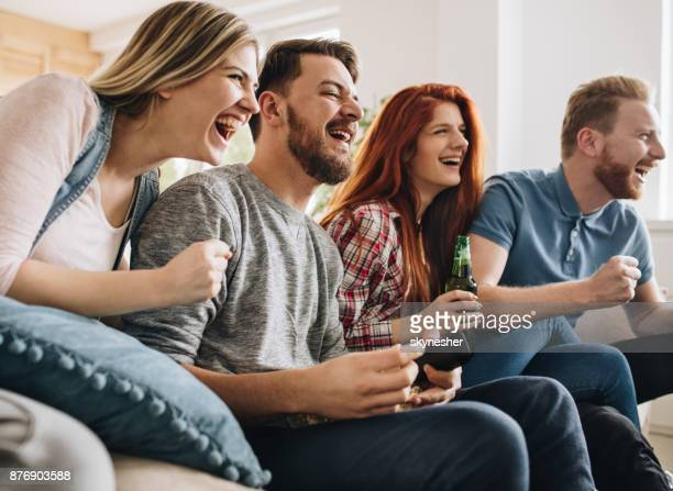 Group of excited friends cheering while watching a game on TV.