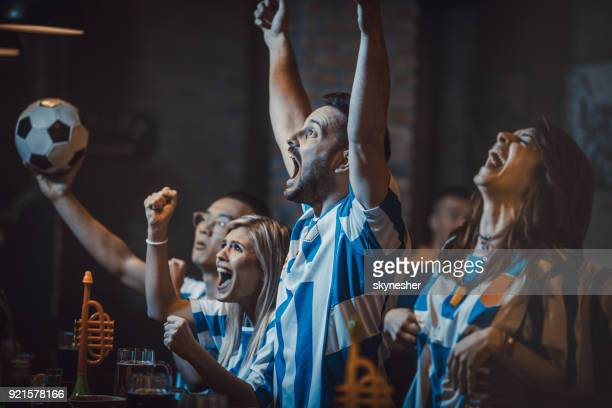 group of excited soccer fans watching successful game on a tv in a bar. - sports jersey stock pictures, royalty-free photos & images
