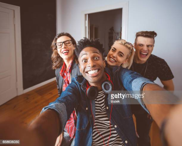 Group of excited young friends taking selfie
