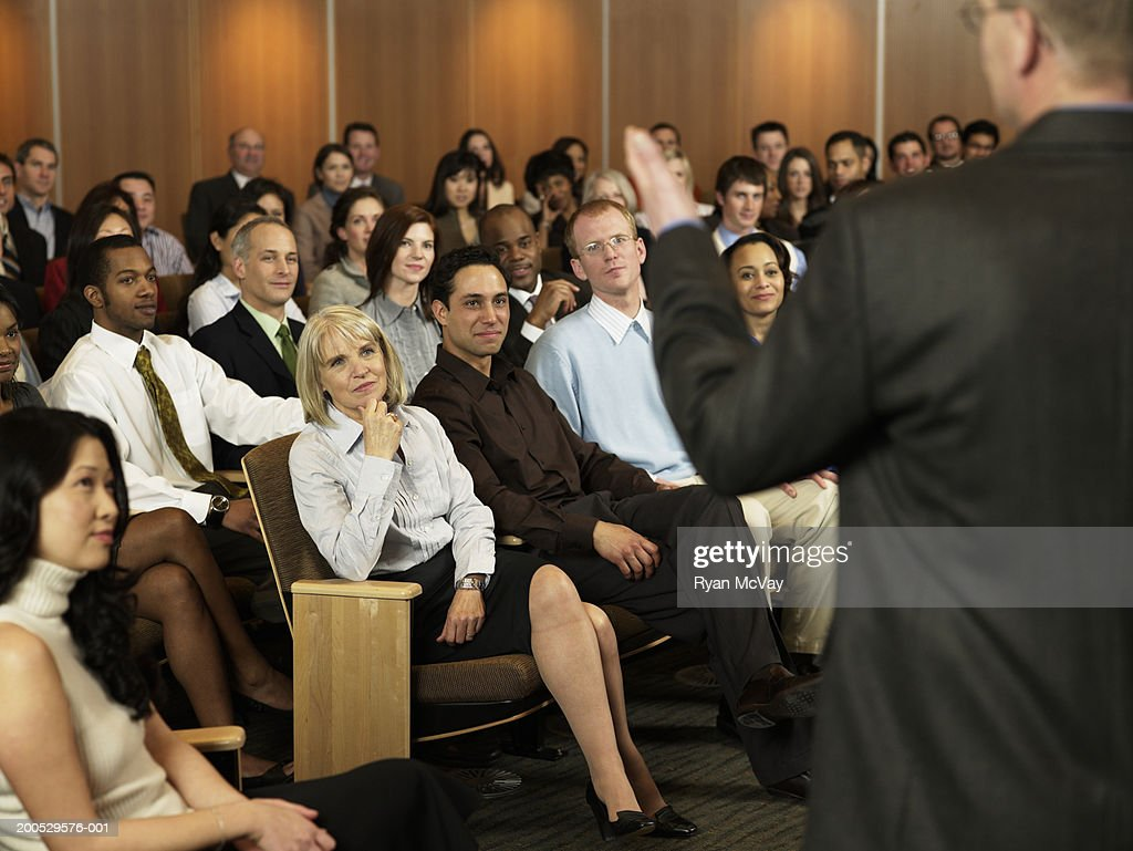 Group of executives listening to man leading seminar in auditorium : Stock Photo