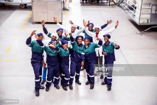 group of factory workers cheering togetherness - labor day stock pictures, royalty-free photos & images