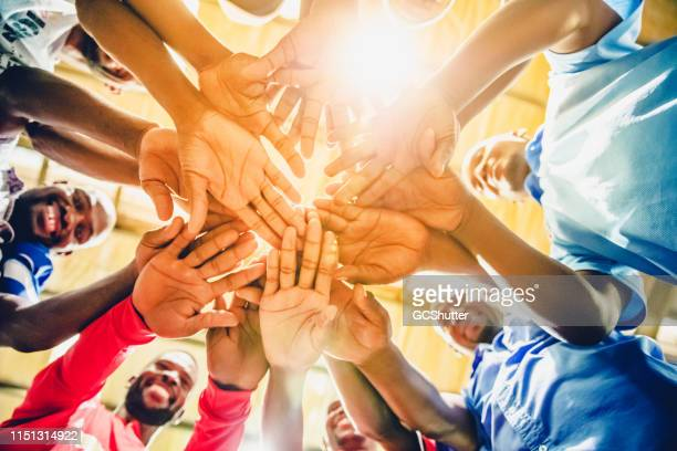 group of factory workers joining hands to express unity - labor day stock pictures, royalty-free photos & images