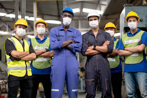 Group of factory workers with mask and two blue collar African-american man and Indian man stand in the front with arm cross and Asian workers in the back