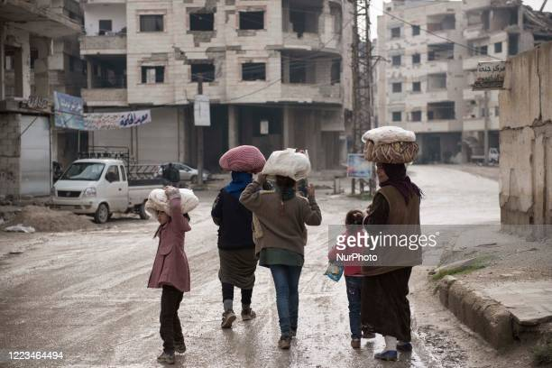 Group of family in Al-Mliha rural of Damascus walking down the street in the way back to home after they brought the bread on January 1, 2020