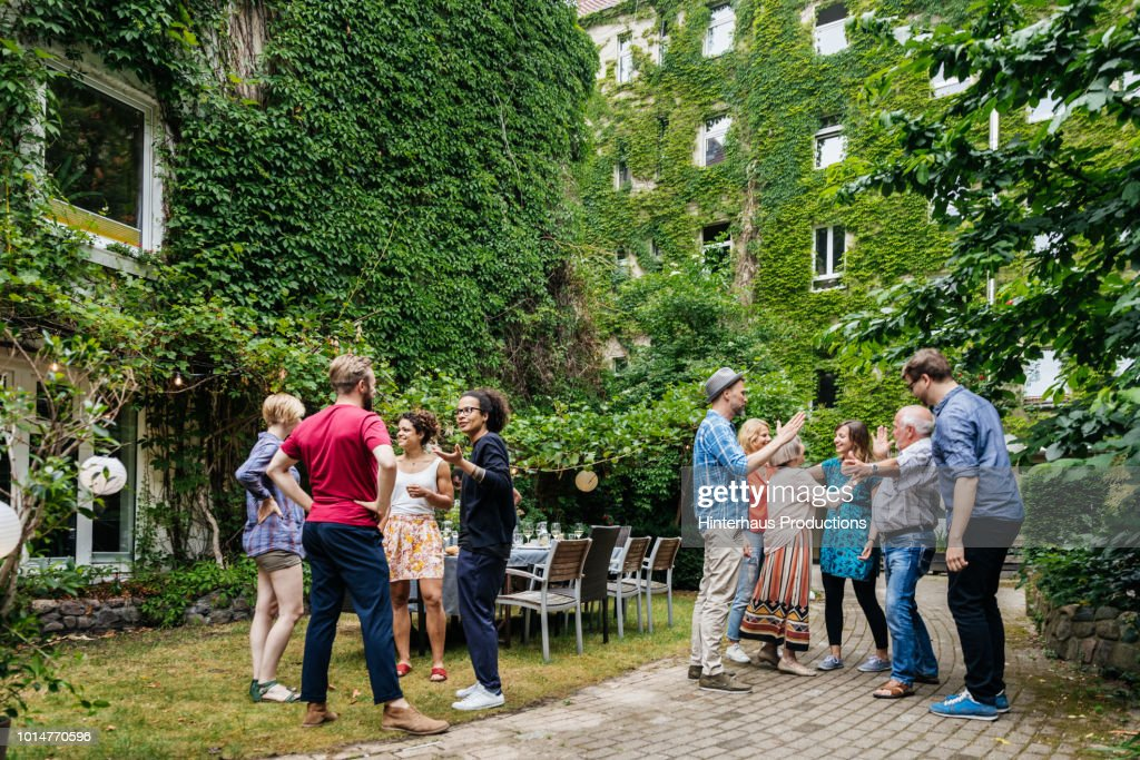 Group Of Family Members Greeting One Another Before Outdoor Meal : Stock Photo