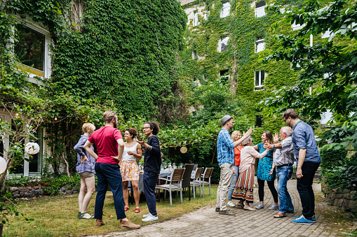 Group Of Family Members Greeting One Another Before Outdoor Meal - gettyimageskorea