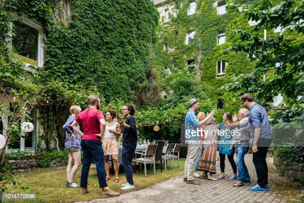 group of family members greeting one another before outdoor meal - mid adult men stock-fotos und bilder
