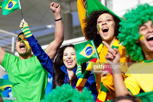 Group of fans cheering for Brazil during a football match.