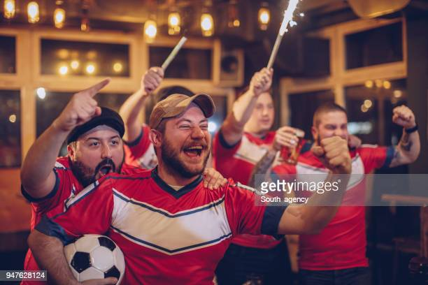 group of fans cheering in pub - hooligan stock pictures, royalty-free photos & images