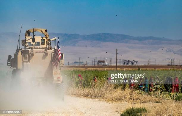 Group of farmers watch as a US military vehicle patrols near the Rumaylan oil fields in Syria's Kurdish-controlled northeastern Hasakeh province, on...
