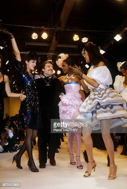 A group of fashion models wear readytowear ruffled cocktail dresses as they applaud French fashion designer Emmanuel Ungaro They modeled the dresses...