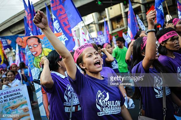 A group of female activists mark International Women's Day with a protest rally on March 8 2014 in Manila Philippines Today around the world...