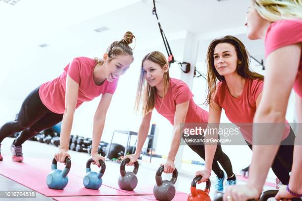 Group Of Female Athletes Doing Plank Exercise With Kettlebells In Gym