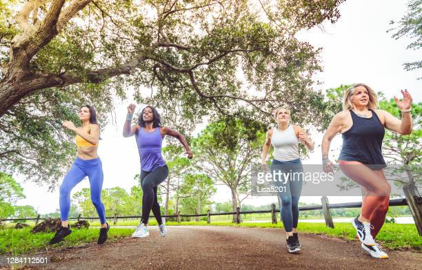 group of female athletes sprinting in a friendly race - friendly match stock pictures, royalty-free photos & images