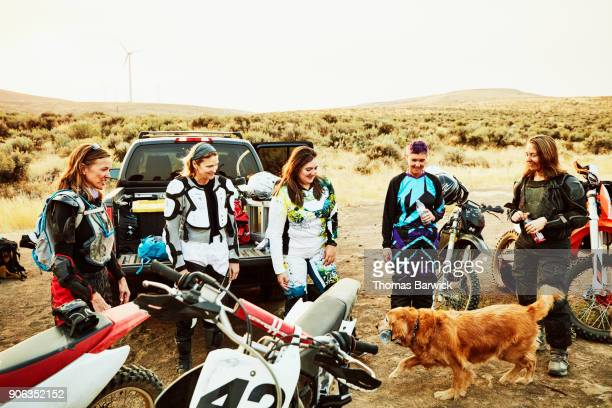 Group of female dirt bike riders relaxing after desert ride on summer evening