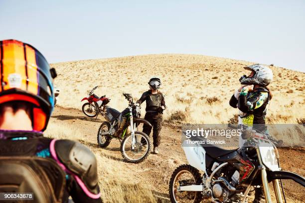 Group of female dirt bike riders resting during desert ride