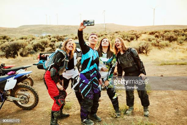 Group of female dirt bike riders taking selfie with smartphone after desert ride on summer evening