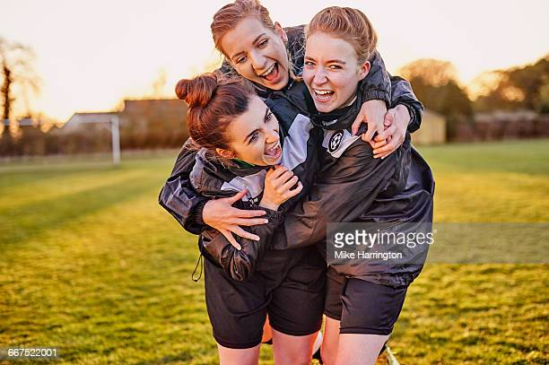 group of female footballers embracing - only young women stock pictures, royalty-free photos & images