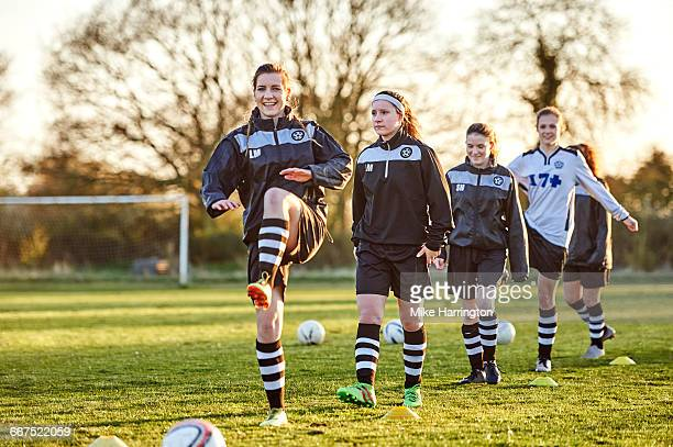 group of female footballers warming up - warming up stock pictures, royalty-free photos & images