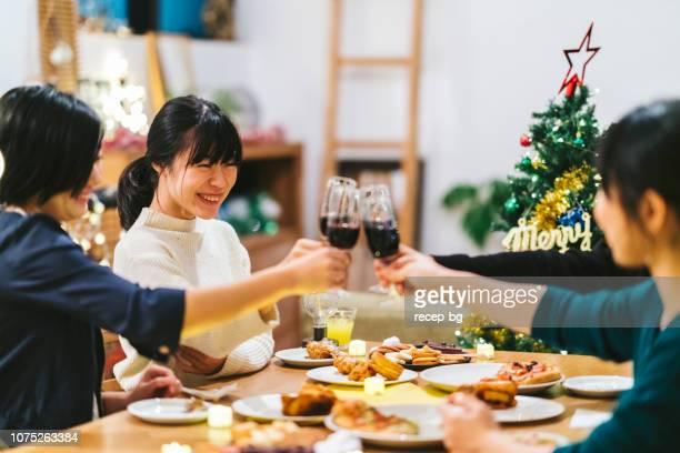 自宅でクリスマス パーティーを楽しんでいる女友達のグループ - ディナーパーティー ストックフォトと画像