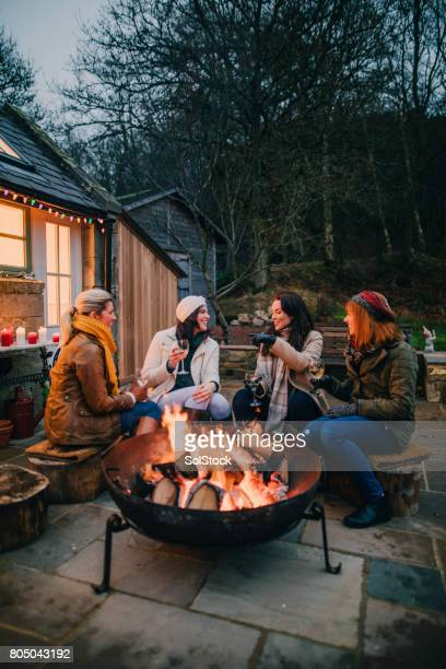 group of female friends gathered around a fire pit - fire pit stock pictures, royalty-free photos & images