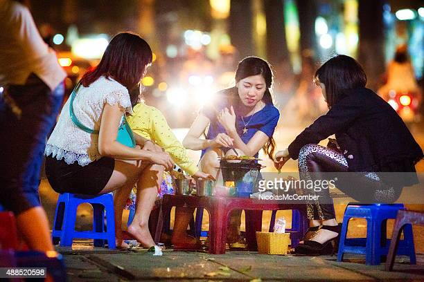 Group of female friends having late barbecue on Hanoi street