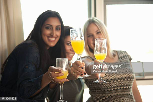 group of female friends holding glasses, making toast - mimosa foto e immagini stock