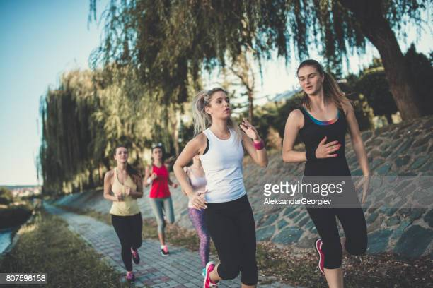 group of female friends jogging at park by the river - aleksandar georgiev stock photos and pictures