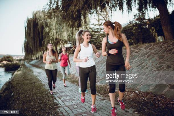 Group of Female Friends Jogging at Park by the River