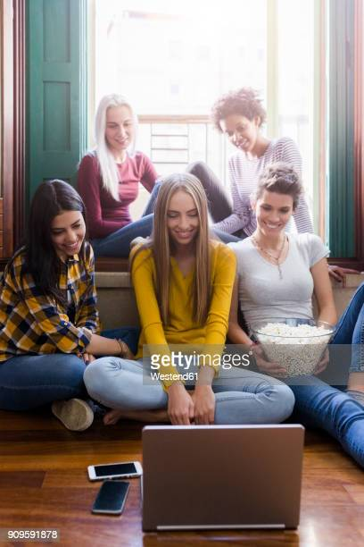 group of female friends looking at laptop together at home - stream stock pictures, royalty-free photos & images