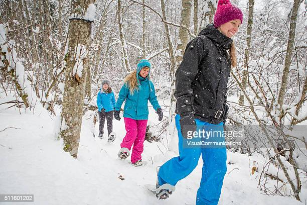 Group of female friends snowshoeing in forest.