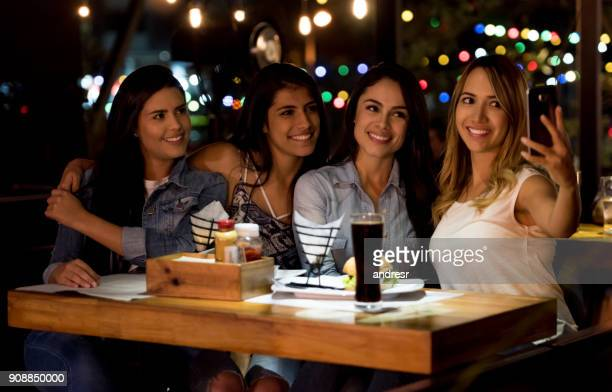 Group of female friends taking a selfie at a restaurant