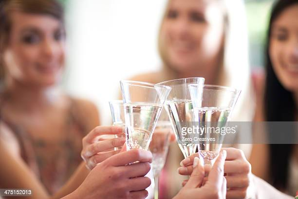 Group of female friends toasting with glass of champagne