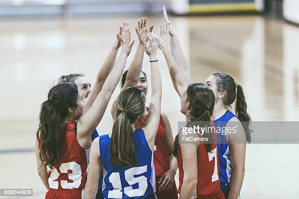 Group of female high school basketball players encouraging one another