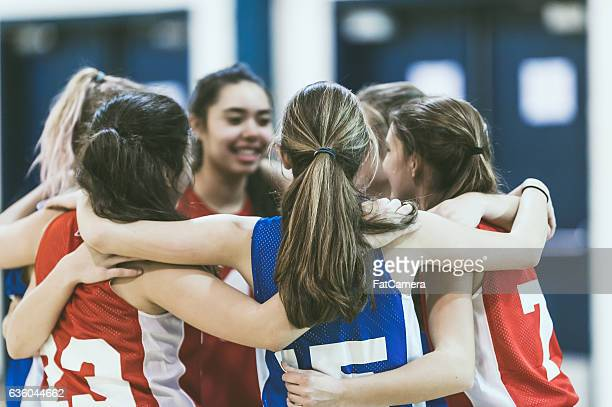 group of female high school basketball players encouraging one another - basketball sport stock pictures, royalty-free photos & images