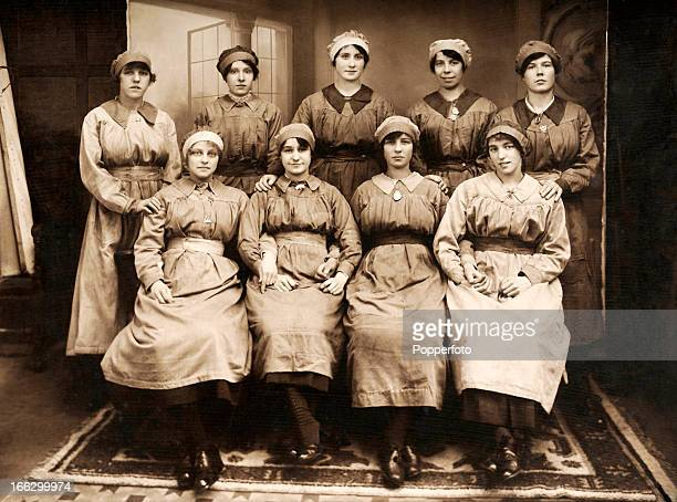 A group of female munitions workers wearing their factory uniforms some also wearing sweetheart badges photographed during World War One circa 1917