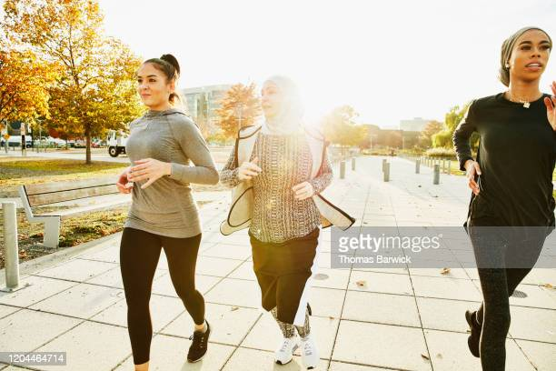 group of female muslim athletes on afternoon run together - black trousers stock pictures, royalty-free photos & images