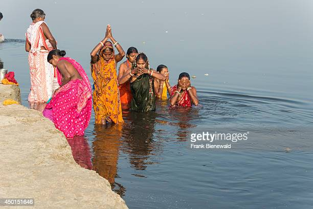 A group of female pilgrims is taking bath and praying in the holy river Yamuna