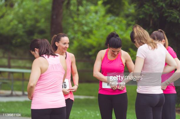 a group of female runners wearing pink prepare to go on a cancer fundraising run together - charity benefit stock pictures, royalty-free photos & images
